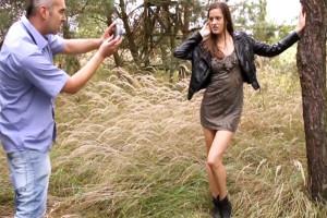 Guapa modelo folla con el fotógrafo en medio del bosque